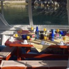 On the covered rear deck of the ship is an inviting table where you can enjoy your meals.